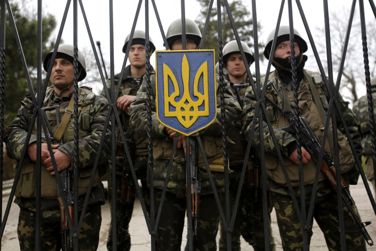 Ukrainian soldiers guard a gate of an infantry base that was surrounded by hundreds of unidentified soldiers, March 2, 2014, in Privolnoye, Ukraine.