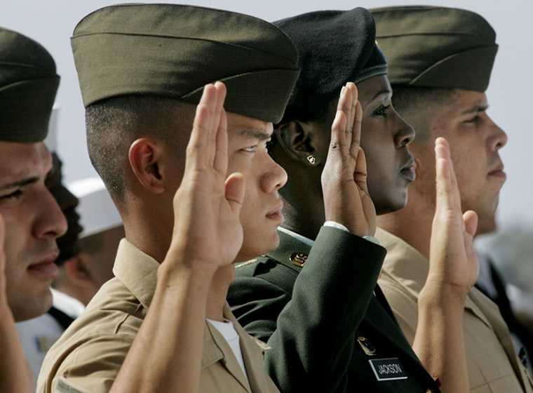 Foreign born citizens in the U.S. military take the Oath of Allegiance aboard the USS Ronald Reagan during a naturalization ceremony at NAS Coronado on Aug. 22, 2006 in Coronado, Calif. (Photo by Sandy Huffaker/Getty Images)