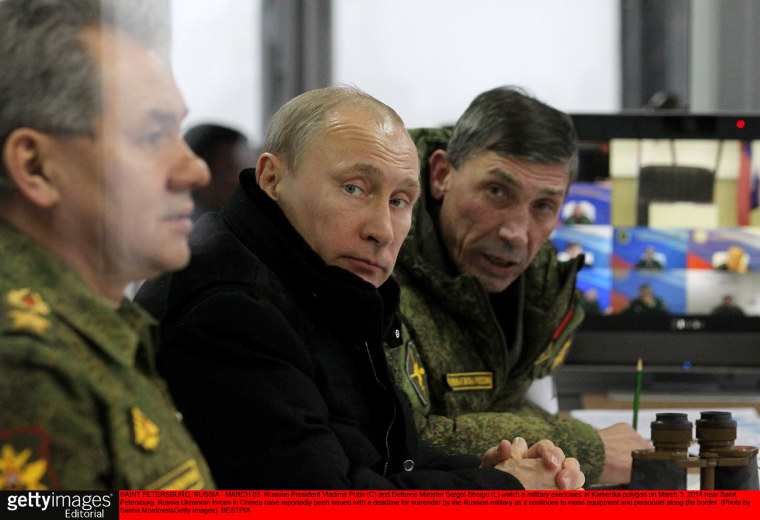 Russian President Vladimir Putin (C) and Defense Minister Sergei Shoigu (L) watch a military exercises at Kamenka polygon on March 3, 2014 near Saint Petersburg, Russia.
