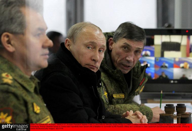 Russian President Vladimir Putin (C) and Defense Minister Sergei Shoigu (L) watch a military exercises at Kamenka polygon on March 3, 2014 near Saint Petersburg, Russia.