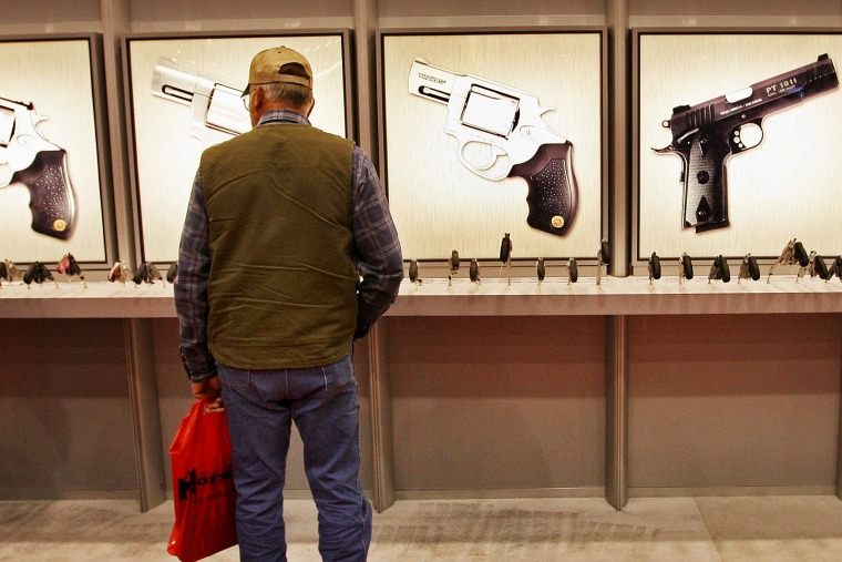 A man looks over the Taurus pistol display at the NRA's annual meeting in in Louisville, Kentucky.