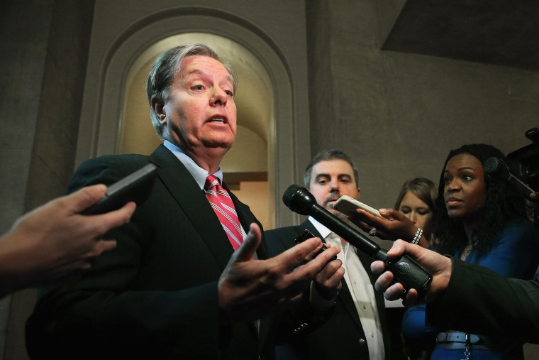 Sen. Lindsey Graham talks to reporters after leaving a Senate Republican caucus meeting at the U.S. Capitol October 11, 2013 in Washington, DC.