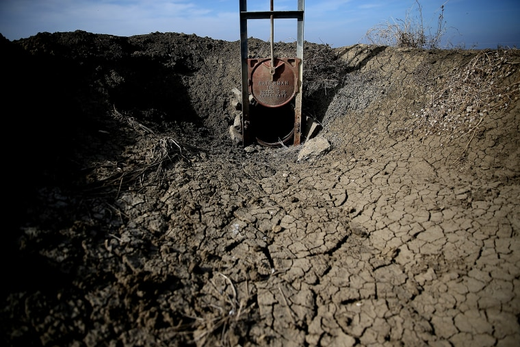 Dried and cracked earth is visible in an irrigation channel on Feb. 25, 2014 in Firebaugh, Calif.