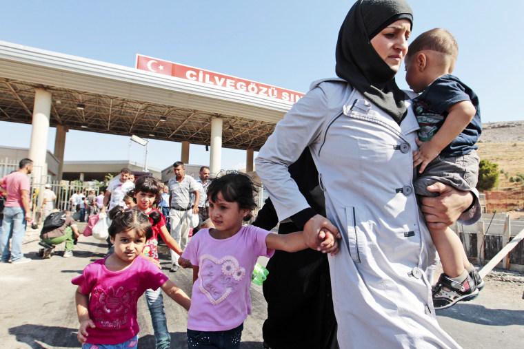 Syrian refugees pass through the Turkish border, Saturday, Aug. 31, 2013.