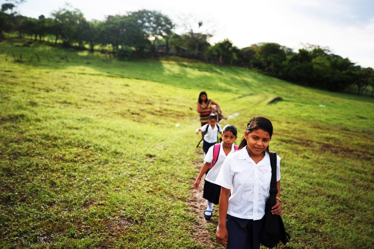 Girls walk to school accompanied by their mother, in the village of Metalio, El Salvador, July 1, 2013.