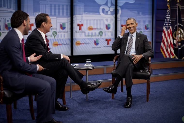 President Barack Obama adjusts his earpiece during a town hall event with television hosts Jose Diaz Balart and Enrique Acevedo, far left, at the Newseum in Washington, on March 6, 2014.