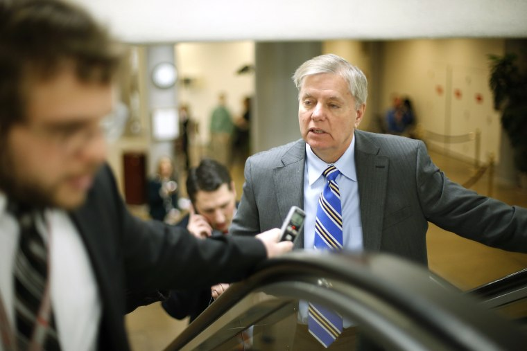 Senator Lindsey Graham (R-SC) (R) talks to reporters as he arrives for the weekly Republican caucus luncheon at the U.S. Capitol in Washington, February 4, 2014.