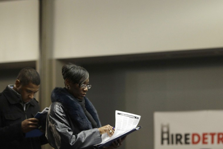 A man and a woman attending a job fair wait in line in Detroit, Mich. on March 1, 2014.