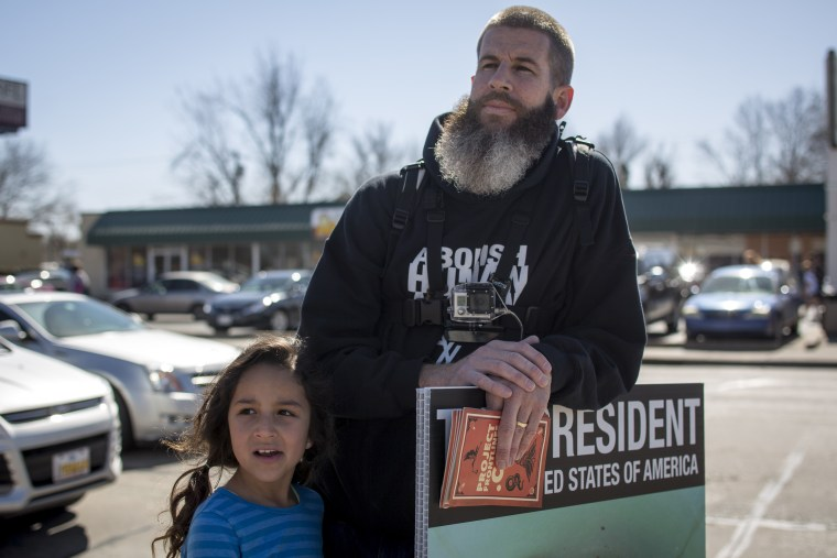 Toby Harmon, member of Abolish Human Abortion, stands with his child outside Norman High School in Norman, Oklahoma on Feb. 21, 2014.
