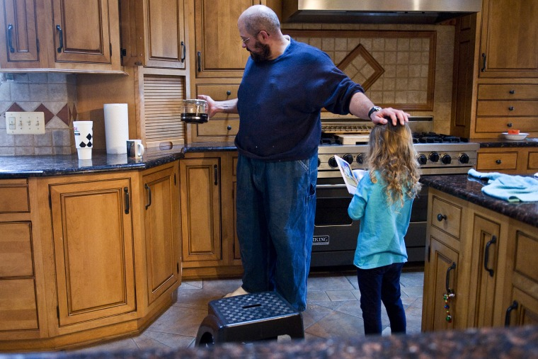 Keith Ohlinger, a stay at home dad and farmer in Maryland, pours a cup of coffee as his daughter Gabrielle, 4, asks him to read a story.