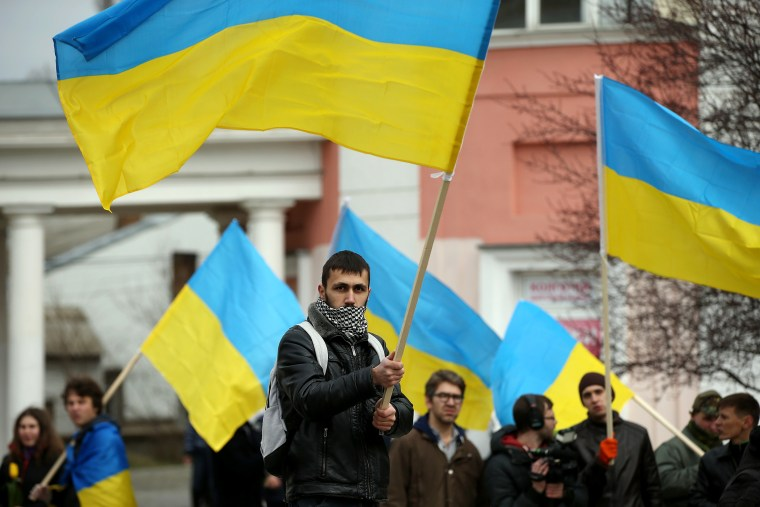 """Pro-Ukrainian sympathizers, waving Ukrainian flags and chanting """"Russian Soldiers Out Of Crimea,"""" """"Glory To Ukraine"""" and """"Crimea Ukraine,"""" gather on March 8, 2014 in Simferopol, Ukraine."""