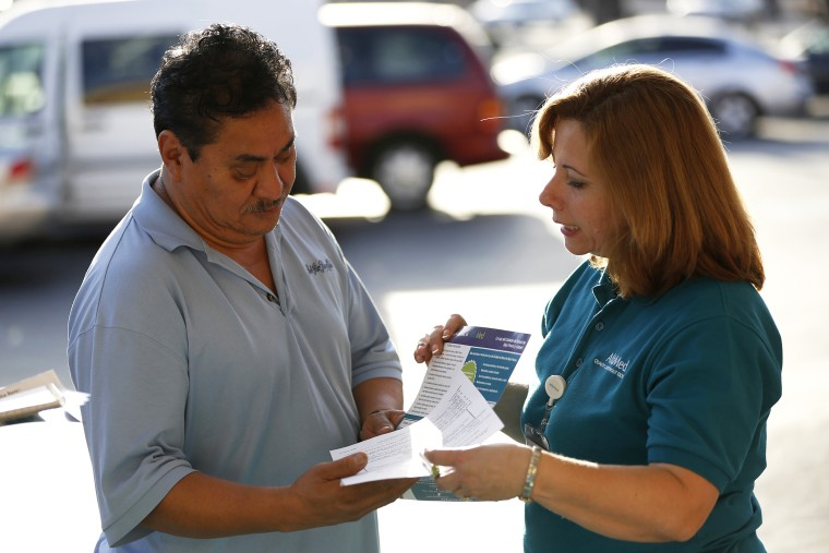 Engrith Acosta, patient care coordinator at AltaMed, speaks to a man during a community outreach on Obamacare in Los Angeles, Calif., Nov. 6, 2013.