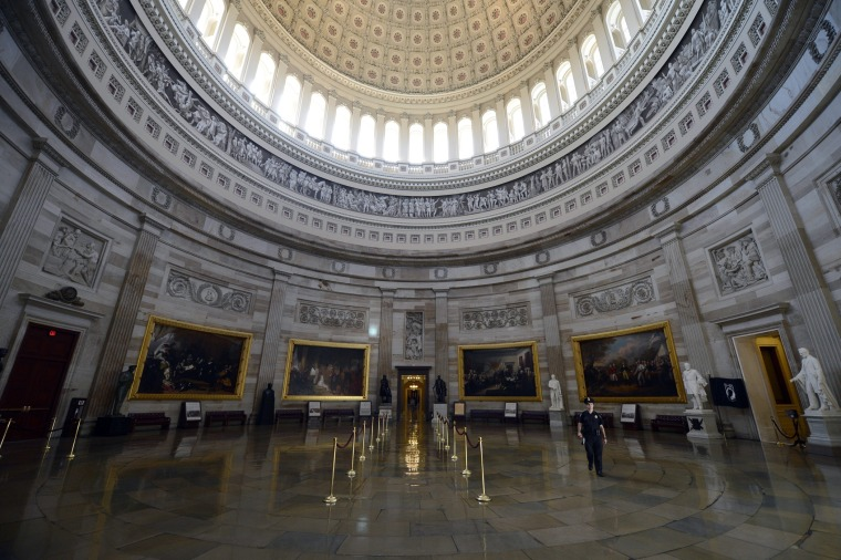 A Capitol police officer walks through the Capitol Rotunda, empty of visitors after being closed to tours, during the government shutdown on Capitol Hill in Washington, D.C., October 1, 2013.