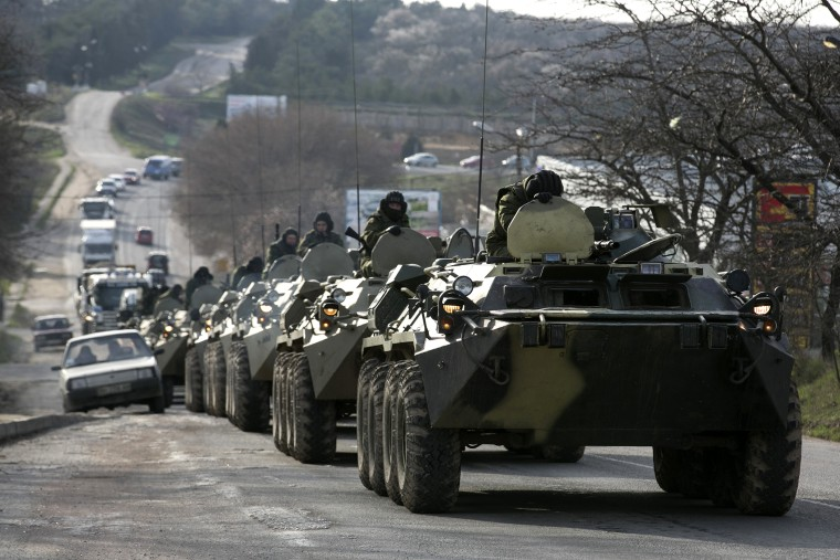 Soldiers, believed to be Russian, ride on military armored personnel carriers on a road near the Crimean port city of Sevastopol on March 10, 2014.
