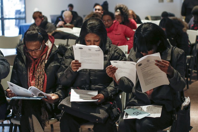 People fill out application forms before a screening session for seasonal jobs at Coney Island in the Brooklyn borough of New York on March 4, 2014.