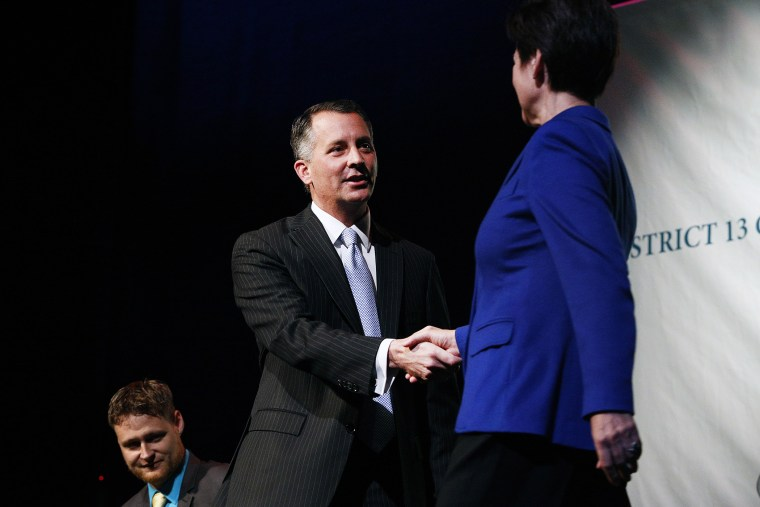 Democrat Alex Sink (C) and Republican David Jolly, both candidates for Florida's congressional District 13, shake hands before participating in a candidate forum in Clearwater, Florida, February 25, 2014.