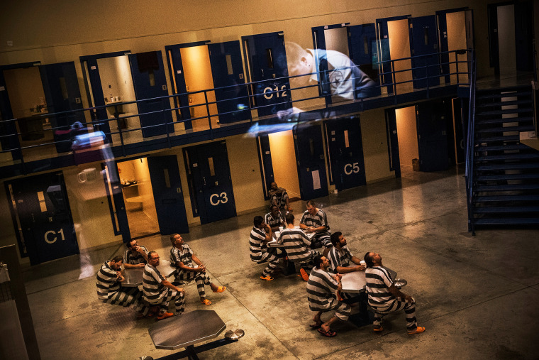 An officer is reflected in the glass as inmates sit in the county jail in Williston, North Dakota, July 26, 2013.