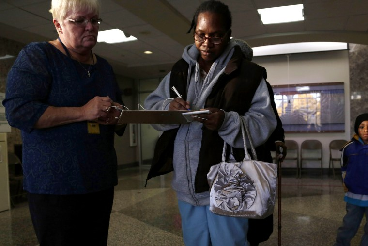 Hezkie Vburgess (C) shows proof of residency to a poll worker during early voting at the Milwaukee Municipal Building on Oct. 22, 2012 in Milwaukee, Wis.