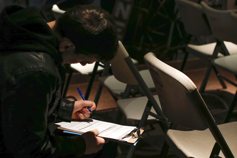 A man fills out paperwork before a screening session for seasonal jobs at Coney Island, March 4, 2014, in Brooklyn, NY.