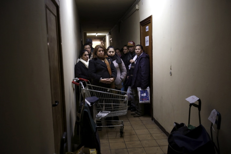 Food bank recipients wait for their cart numbers to be called out to pick up their donated food on distribution day at Madrid's Tetuan food bank in Madrid, Spain on Dec. 10, 2013.