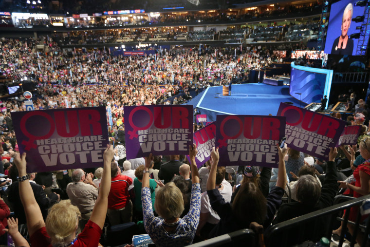People hold signs as president of Planned Parenthood Federation of America, Cecile Richards, speaks during the Democratic National Convention on September 5, 2012 in Charlotte, North Carolina.