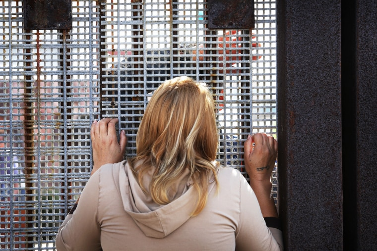 Family members reunite through bars and mesh of the U.S.-Mexico border fence at Friendship Park in San Diego, Calif., Nov. 17, 2014.