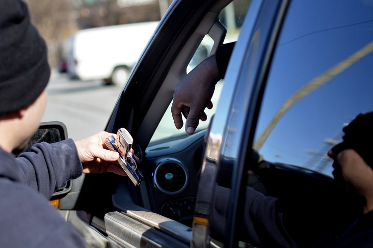 A police officer collects a gun from from a motorist during a gun buyback, in Atlanta, Georgia, Jan. 16, 2014.