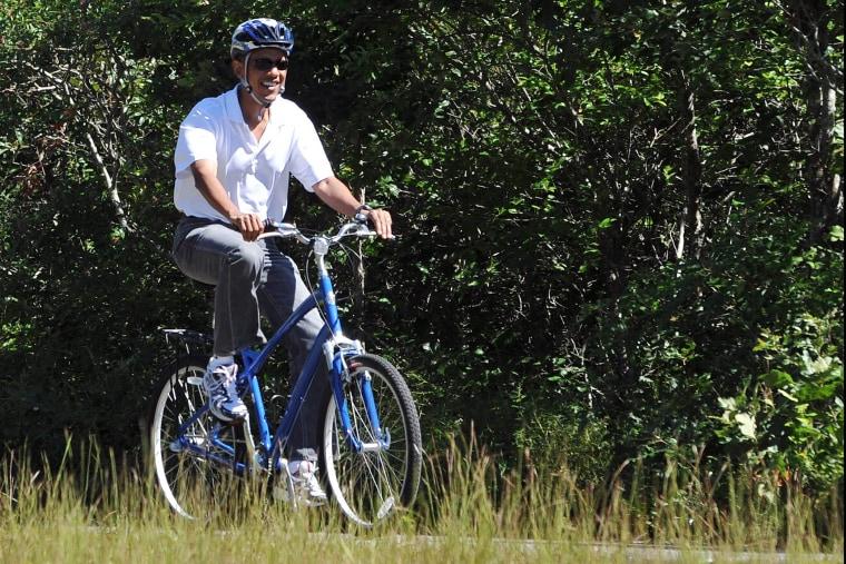 US President Barack Obama rides his bicycle in West Tisbury on Martha's Vineyard, Massachusetts, on Aug. 27, 2010.