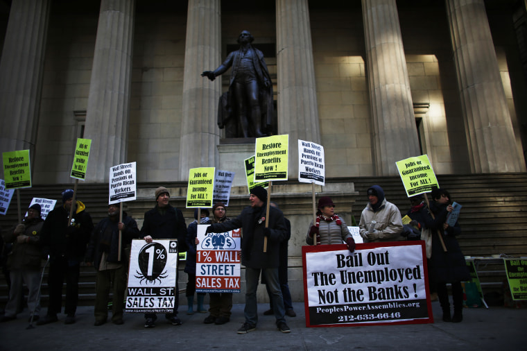 Members of Occupy Wall Street and People Power Assembly take part in a protest demanding restoration of extended unemployment benefits next to the New York Stock Exchange in New York