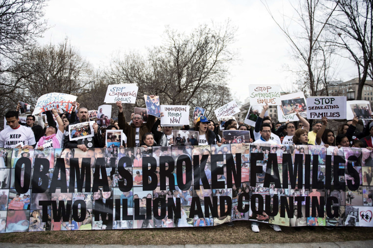 Activists hold signs and family photos in Lafayette Square outside the White House March 12, 2014 in Washington, D.C.