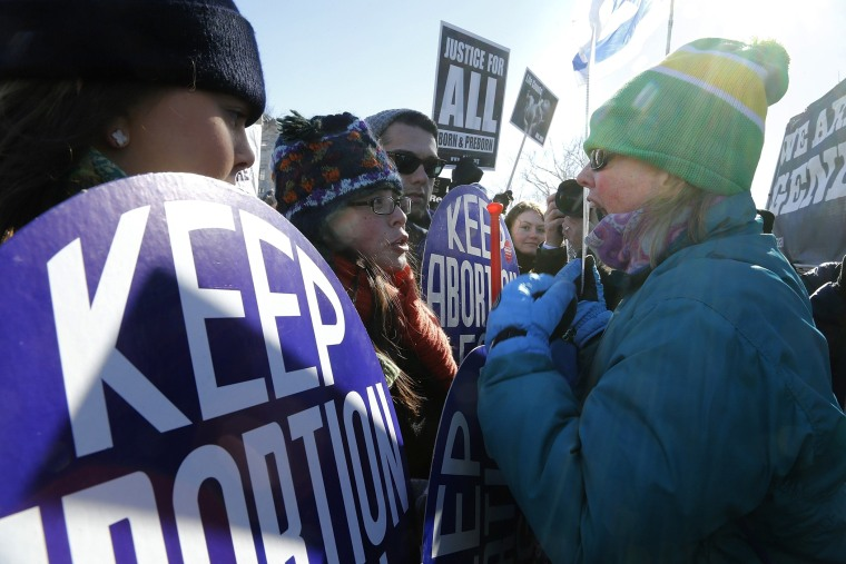 An anti-abortion demonstrator (R) shouts at pro-choice demonstrators (L) in front of the U.S. Supreme Court during the annual March for Life in Washington, January 22, 2014.