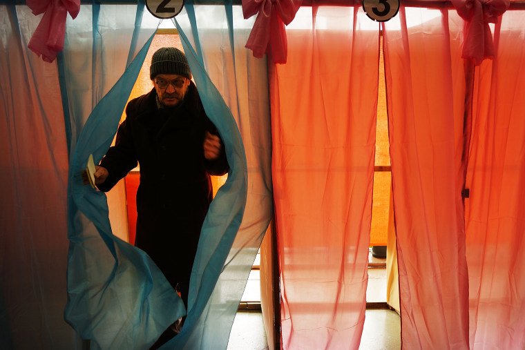 A man exits a polling booth with his ballot paper inside a polling station on March 16, 2014 in Perevevalne, Ukraine.