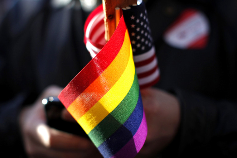 A marriage equality supporter holds gay pride and American flags at a demonstration.