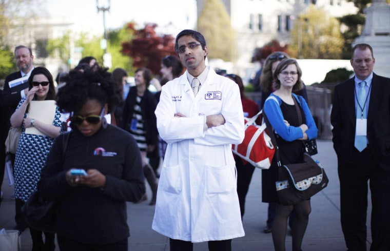 Doctor Vivek Murthy stands among other bystanders during the first day of legal arguments over the Affordable Care Act outside the Supreme Court in Washington March 26, 2012.