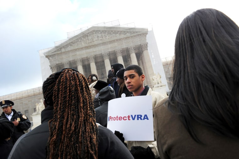 An activist holds a pro-voting rights placards outside of the US Supreme Court in Washington, DC, Feb. 27, 2013.