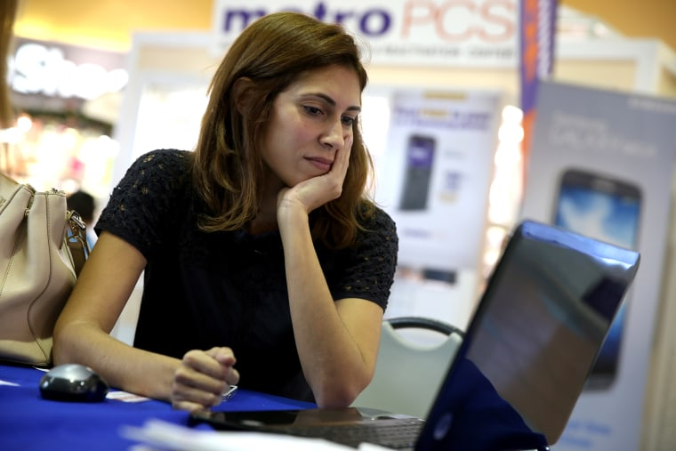 Maritza Martinez works with an insurance agent to purchase health insurance under the Affordable Care Act on Dec. 22, 2013 in Miami, Fla.