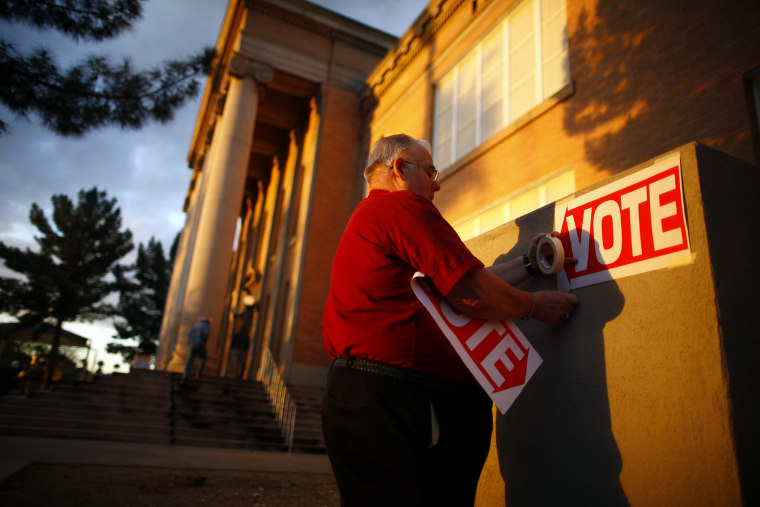 A poll worker posts signs at a polling station, Feb. 28, 2012, in Phoenix, Ariz.
