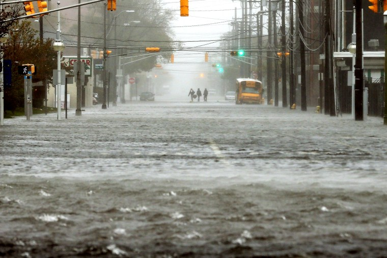 People walk down a flooded street as Hurricane Sandy moves up the coast on Oct. 29, 2012 in Atlantic City, N.J.