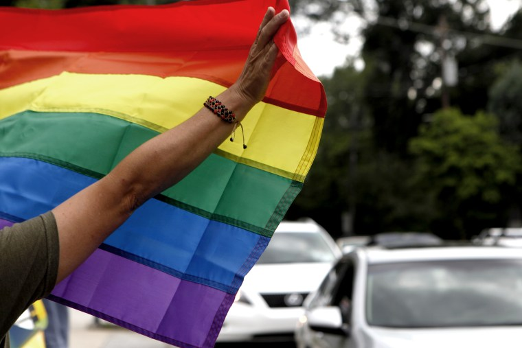 Atlanta resident River Moore holds up a rainbow flag while celebrating of the U.S. Supreme Court's rulings same-sex marriage on June 26, 2013, in Atlanta, Ga.