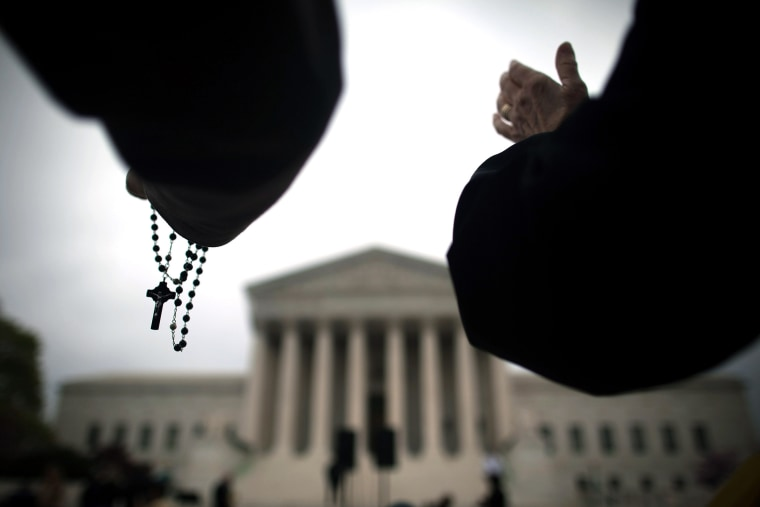 Religious activists lead a prayer vigil outside the Supreme Court on March 25, 2012 in Washington, DC.