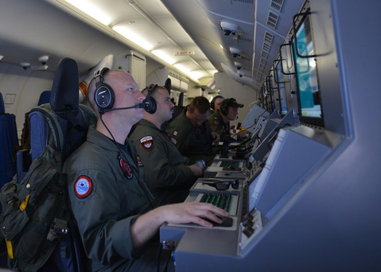 This March 16, 2014 US Navy handout image shows crew members on board a P-8A Poseidon assigned to Patrol Squadron (VP) 16 man their workstations while assisting in search and rescue operations for Malaysia Airlines flight MH370.