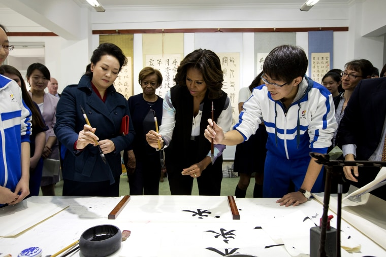 Peng Liyuan (L), wife of Chinese President Xi Jinping, shows First Lady Michelle Obama how to hold a writing brush as they visit a Chinese traditional calligraphy class at the Beijing Normal School, March 21, 2014 in Beijing, China.