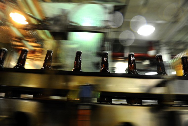 Bottles speed by after being filled in the bottling area of the Coors brewery in Golden, Colo.
