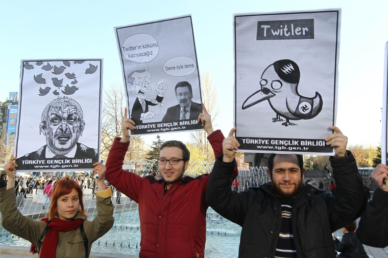 People hold placards as they protest against Turkey's Prime Minister Tayyip Erdogan after the government blocked access to Twitter in Ankara, on March 21, 2014.