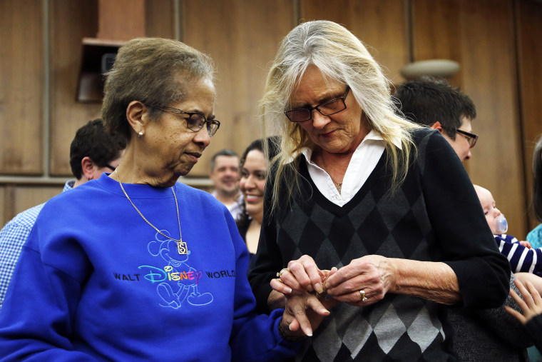 Pennye Mattson, right, places a wedding ring on Sherrie Tyler, left, while being married in a group by the Oakland County Clerk in Pontiac, Mich., March 22, 2014.