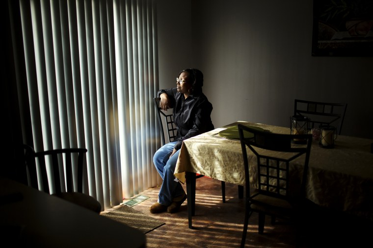 Renee Brooks looks out of the window in her home in District Heights, Maryland.