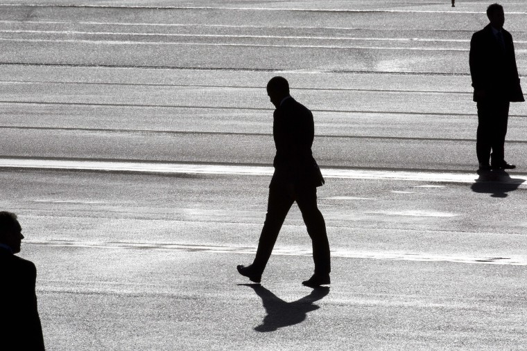 President Barack Obama (C) and two secret service agents are silhouetted as he walks towards Marine One helicopter as they arrive at Schiphol Amsterdam Airport