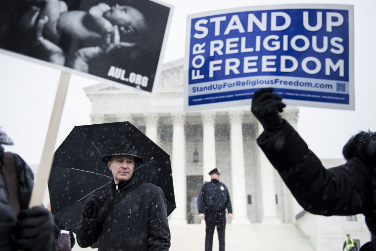 People who support Hobby Lobby's choice to withhold contraceptive healthcare coverage from their employees rally outside the US Supreme Court, Mar. 25, 2014.
