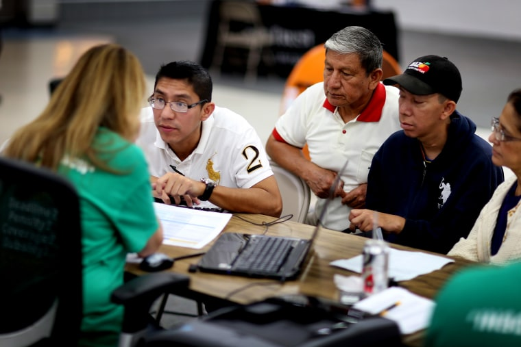 Paul Paucar (L-R), Homero Paucar, Giovanny Paucar and Ivonne Cucalon sit with Jessica Adames to purchase health insurance under the Affordable Care Act on March 20, 2014 in Miami, Fla.
