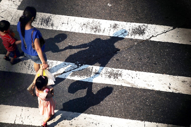 A woman crosses a street with children as seen from the Manhattan Bridge in New York City, on Aug. 21, 2013.